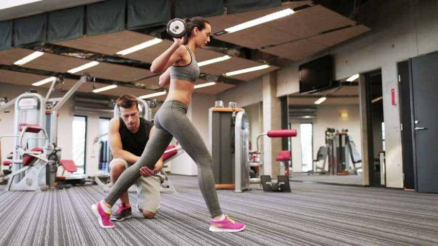 sport, fitness, lifestyle, weightlifting and people concept - woman and personal trainer doing lunge with barbell and flexing muscles in gym