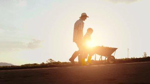 Farming father helping son push wheelbarrow up hill on their farm at sunset.