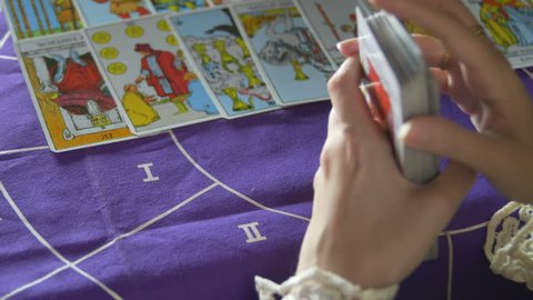 Tarot reader dealing cards & reading future and fortune. Day. Window & trees background. Modern. White dress. Close Up. Over the Shoulder