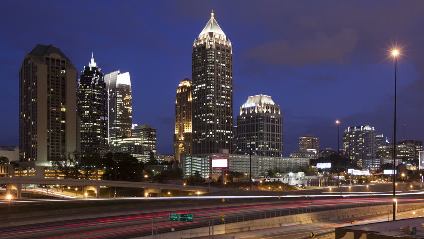 4K Time lapse close up Atlanta downtown skyline during twilight blue hour with traffic passing by on highway