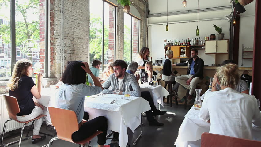 Many Young People Talking in Bright Stylish Restaurant