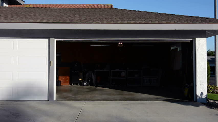 a residential home with an automatic roll up garage door moving in the closing position