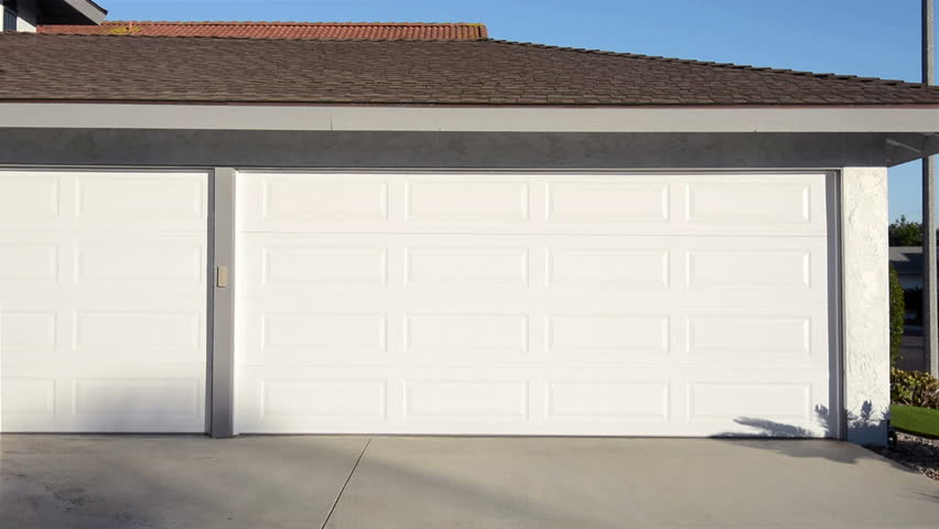 a residential home with an automatic roll up garage door moving in the opening position