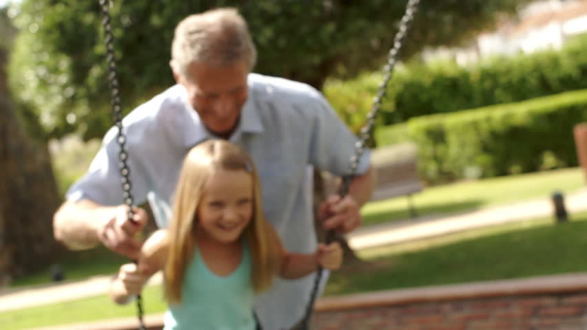Slow-Motion Of Grandfather Pushing Granddaughter On Swing In Park.