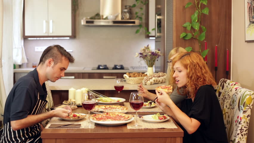 Group Of Happy Friends Eating Pizza In Dining Room At Home