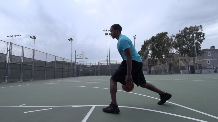 A young man playing basketball on a rainy day. - Super Slow Motion - Model Released - 1920x1080 - HD - filmed at 240 fps