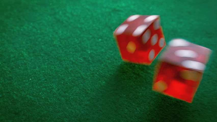 Pair of dice rolling in slow motion at casino