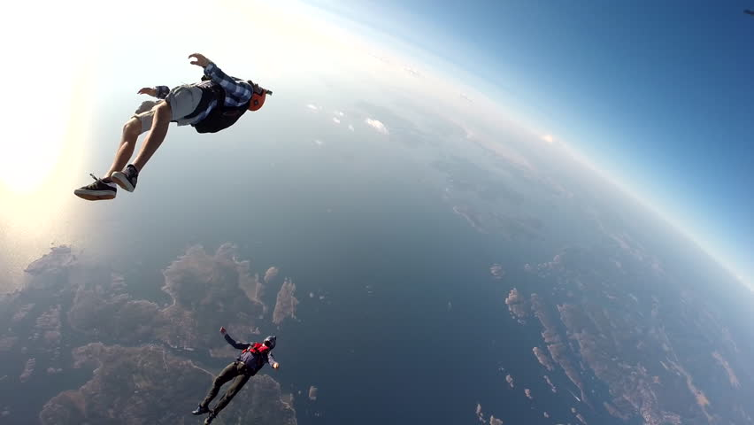 A group of skydivers jump together from a plane before skydiving over a landscape surrounded by a water body, POV #8257348