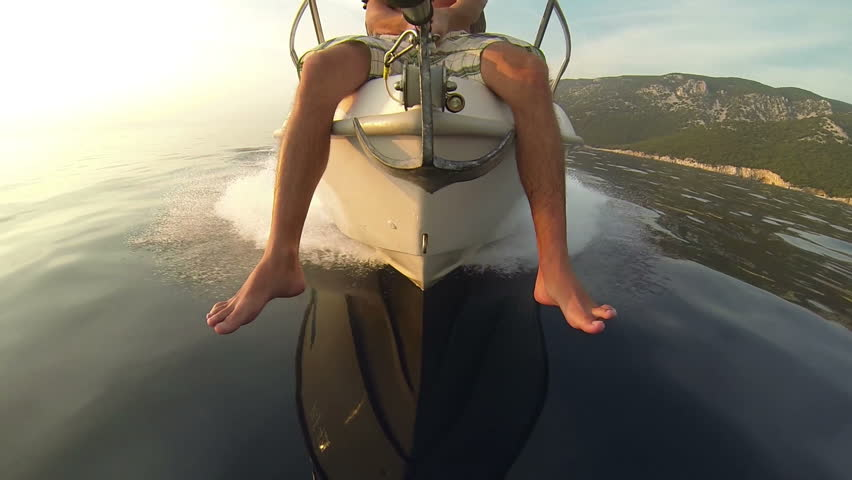 GoPro, slow motion - Man sitting on a speedboat bow while sailing on water