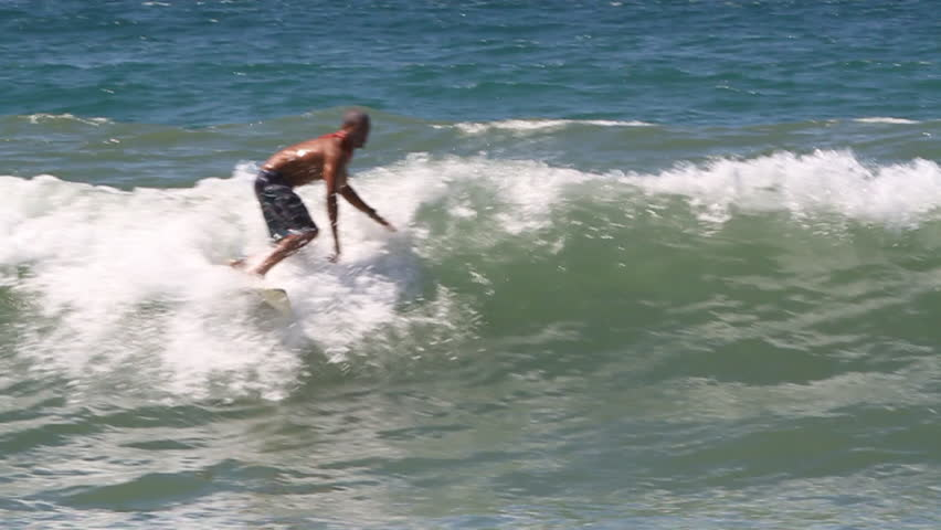 A surfer performs an aerial maneuver, tries to maintain balance but loses and falls into water | Shutterstock HD Video #8303338