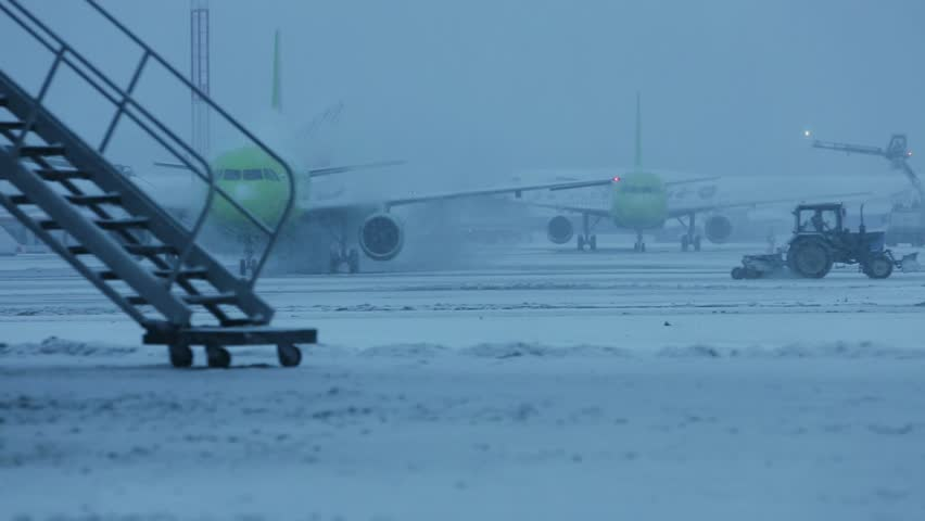 Snowstorm at the airport. Preparation protective treatment of aircraft icing