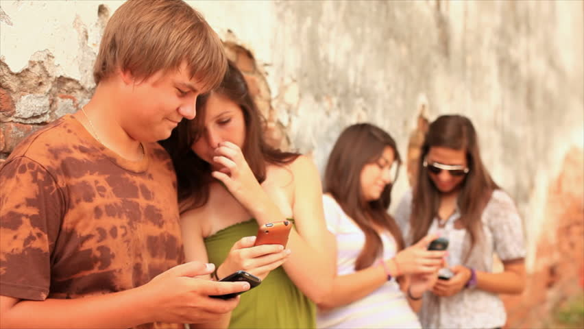 A group of teenagers hanging out by an old brick wall, using cell phones to send text messages and talking to each other.