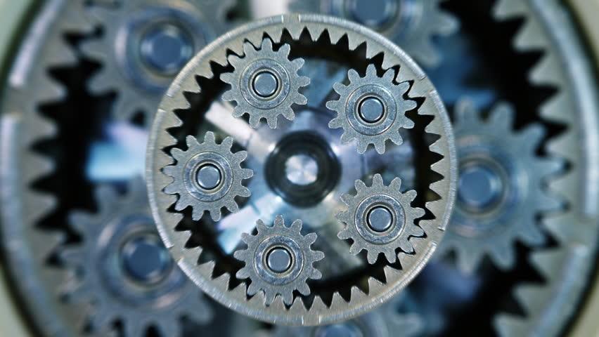 Movement of metal gears in a mechanical device. Brass pinion mechanism. Closeup