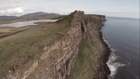 Cinematic aerial shot looking over the edge of a cliff on Skye in Scotland with a dramatic coastline