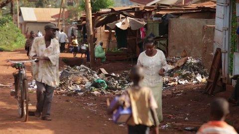 LUWERO, UGANDA - SEPTEMBER 2013: People walking past a rubbish tip in Uganda, Africa