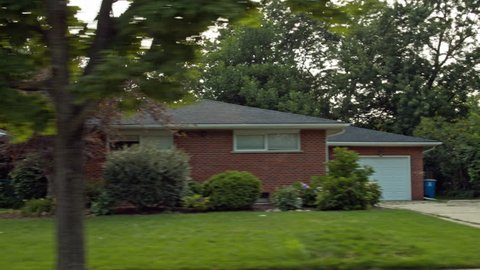 Driving plate: right view (driver side), 1950s-70s single-storey, ranch-style houses in Mid West US neighborhood.  Intended for compositing.  24mm lens, stabilized clip, moderate speed, 4K, UHD.