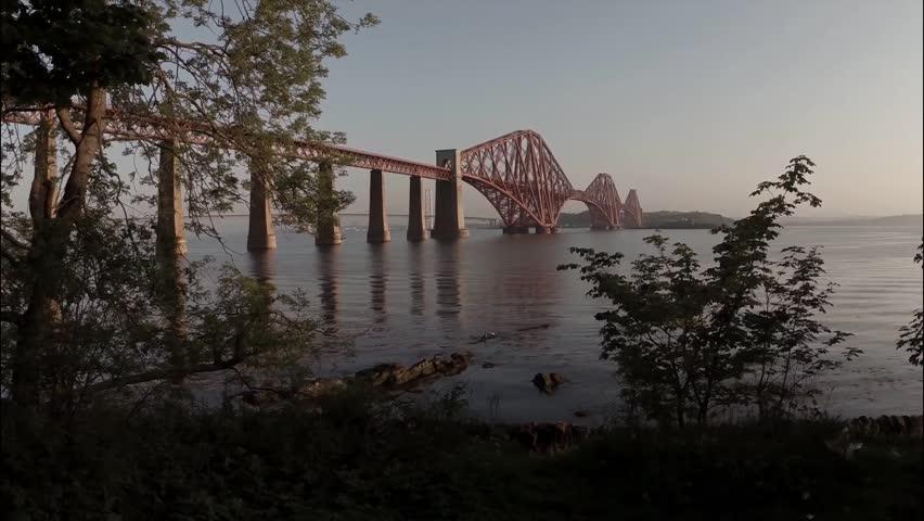 EDINBURGH, SCOTLAND - MAY 2014: Aerial shot revealing the Forth Rail Bridge outside Edinburgh during sunrise on a calm summer morning