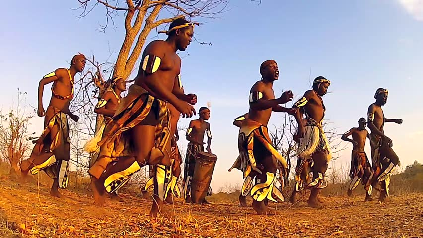 Traditionally dressed African tribesmen of the Herero Tribe dance and sing songs of welcome in Victoria Falls, Zimbabwe, Africa. Drumming, jumping, clapping & singing abound amongst this happy group.