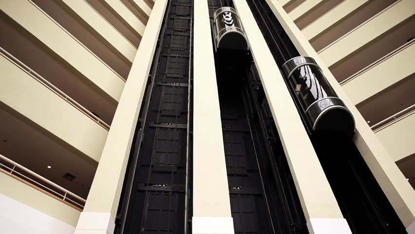 Elevators in lobby of luxury hotel moving up and down in modern architecture