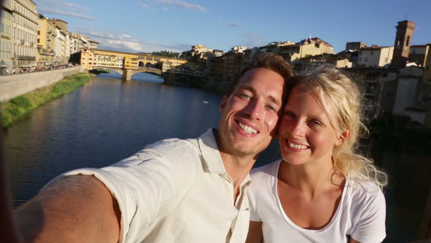 Selfie - Happy couple selfies photo on travel in Florence. Romantic woman and man in love smiling happy taking self portrait by Ponte Vecchio during vacation holidays in Florence, Tuscany, Italy.