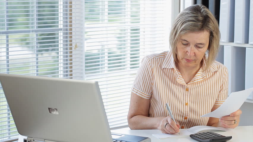 Middle Age Woman Writing A Check To Pay Bills In Her Home Office