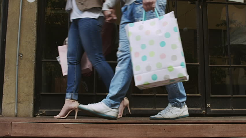 Side view of happy young couple walking with shopping bags and holding hands while woman pulls him around from shop to shop. . Steadicam shot.