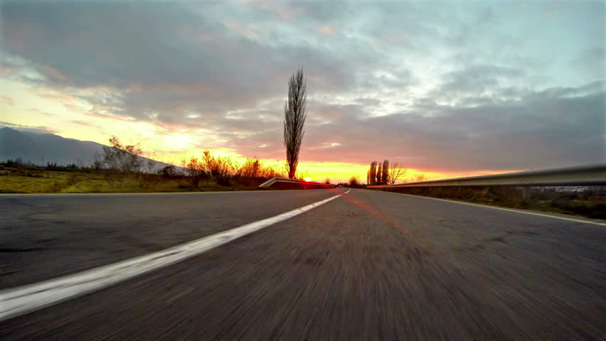 UHD Sport car driving on a country road sunset. Wheel spinning POV - Point of View, sunrise. Trees on the side. Fast motion speed. 4k shoot