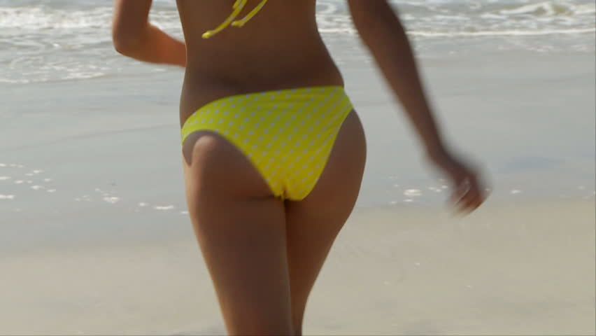 Woman in yellow bikini running out of the water at the ocean