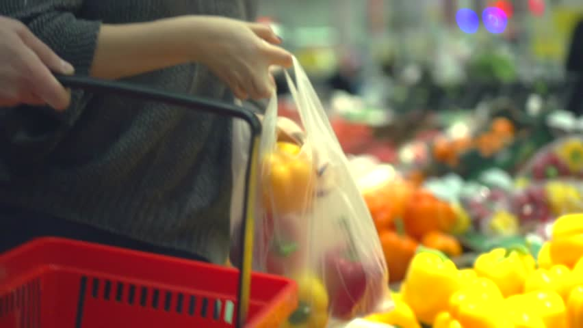 Happy couple in Supermarket buying fresh vegetables, choosing fresh vegetables in super market. Smiling People select red and yellow pepper putting it to shopping cart. Grocery store. HD 1080p  | Shutterstock HD Video #8485258