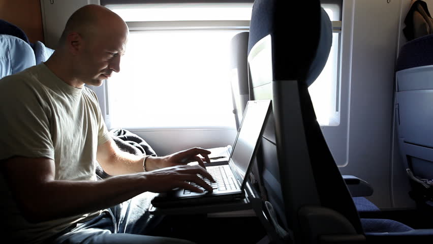 A middle-aged man is working with a laptop during a train ride, nice light effects by sunlight from a big window he is next to