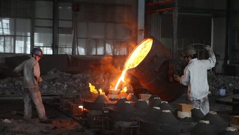 Shanghai,China-July 10,2012: chinese metallurgy worker pouring melting steel liquid into the mold.