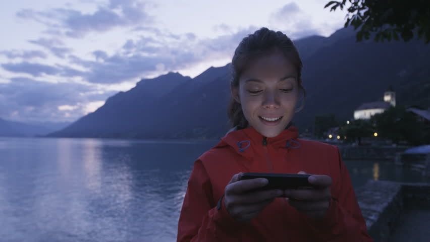 Smartphone and sms text message - woman texting using smart phone app at night by lake. Nighttime footage of girl using smart phone app on cellphone outdoors by Lake Brienz in Brienz, Switzerland.