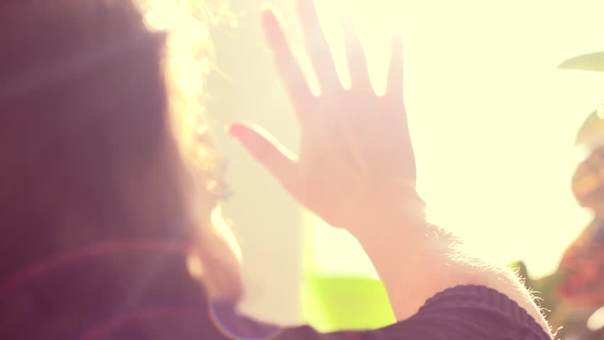 Girl touching the sunlight by hand in her room at home. Happy woman looking at shining sun through her fingers. Slow motion video footage high speed camera 240 fps, slowmo, full HD 1920x1080p