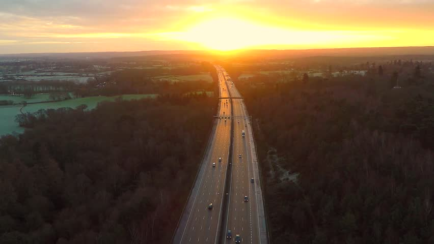 Aerial view of a truck and other traffic driving along a road at sunrise
