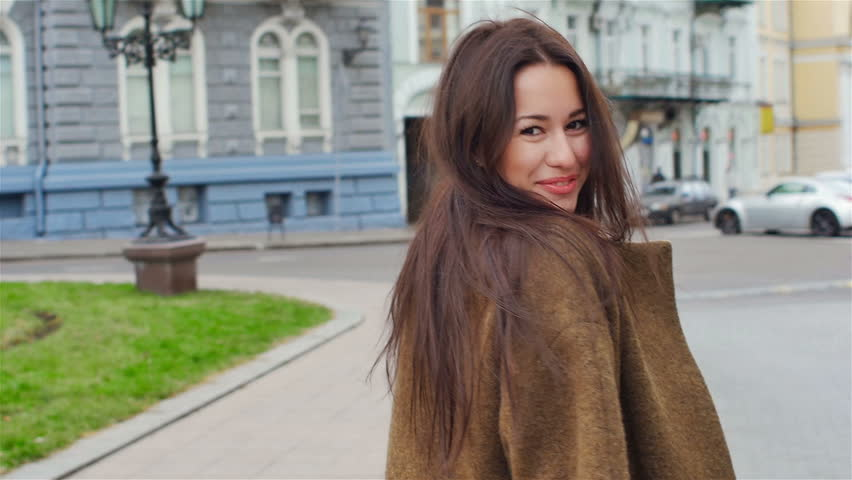 Young, beautiful, attractive woman in a stylish coat walks through the city streets. She laughs, poses for the camera, her hair blowing in the wind, looking very happy. slow motion