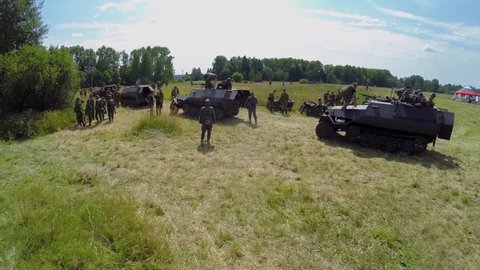 NELIDOVO - JUL 12, 2014: Soldiers of soviet and german armies on vehicles during reconstruction Battlefield at sunny day. Aerial view