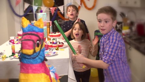 Boy hitting a pinata at party while his friends cheer him up in slow motion