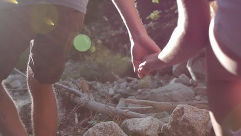 Closeup Of Young Couple Holding Hands, And Running Through The Forest (Lens Flare, Slow Motion)