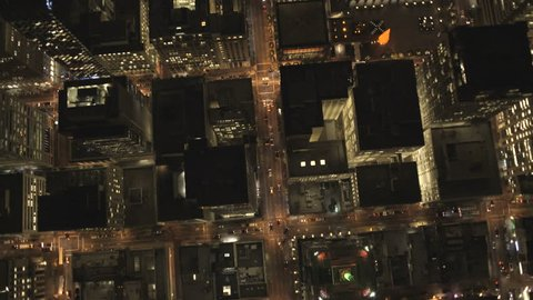 Aerial overhead rooftop view at night city road traffic illuminated by city streets skyscrapers San Francisco California USA 4K