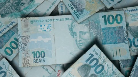 An extreme close up pan of a pile of randomly scattered brazilian real banknotes