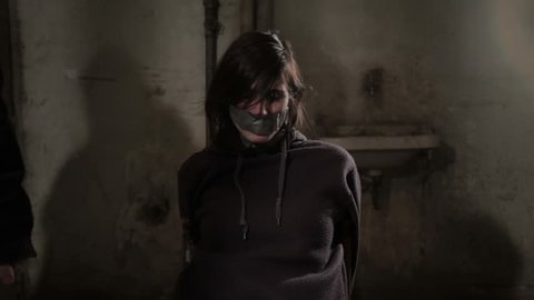 Two kidnappers hijacking beaten female hostage and tied her to chair in dirty dark basement. One of the abductors (hijackers) put duct tape on her mouth. Victim of kidnapping and human trafficking.