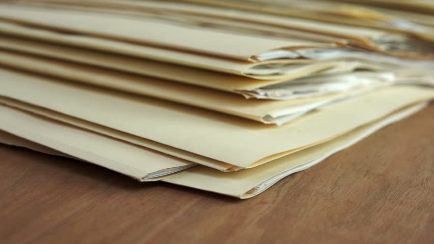 Dolly shot of messy file folders with papers sticking out laying flat on a table in a pile. | Shutterstock HD Video #8704438