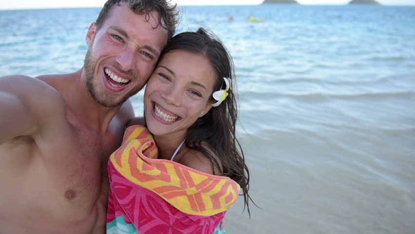 Romantic Couple Taking Selfie Portrait Video Picture On Beach With Camera Or Smart Phone Wearing Towel