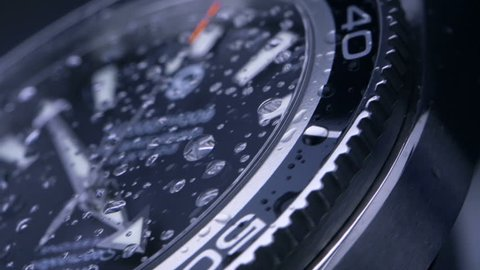 Wrist watch - slow motion / time passing slowly - beautiful macro shot with little drops of water on the glass