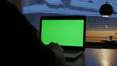 Man watching (Green Screen) Laptop. Pointing at the screen at the end. In Home Office.