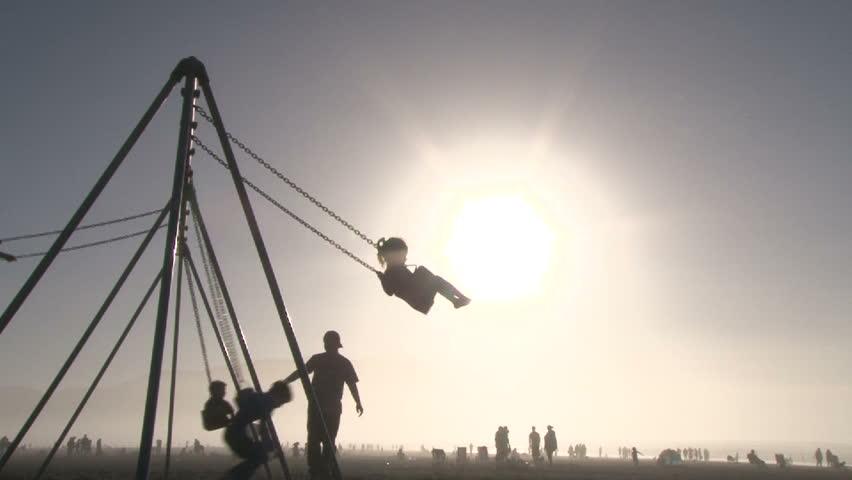 Silhouetted children enjoying beautiful sunny day playing on swing set in Seaside, Oregon.