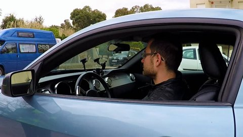 young handsome man driver undertaking clinical test for alcohol content state using a breathalyzer