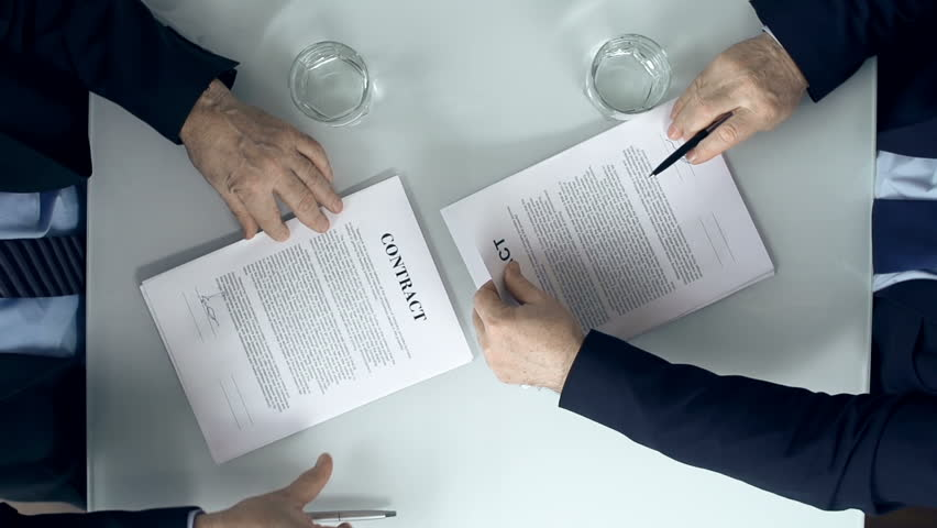 Direct from above view of two business parties signing respective copy of a contract and congratulating each other with firm handshake