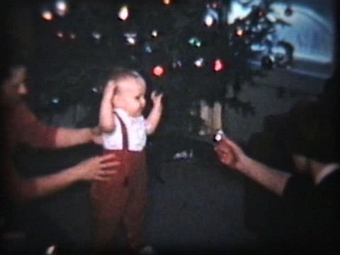 A cute baby boy with red suspenders tries to walk towards a shiny Christmas decoration.