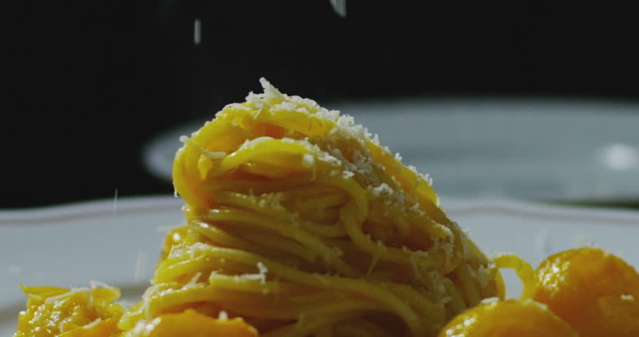 Super slow motion macro of grating a Parmigiano-Reggiano cheese on spaghetti pasta in the white plate (close up)